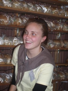 Sarah Beth Slabach takes a break in front of the shelves of loaves.