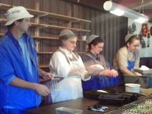 Matt and Loretta Burkey, Rachel Burkey Miller and Darla Orendorf Kremer shape and prick the loaves.
